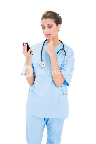 Troubled brown haired nurse in blue scrubs using a mobile phone