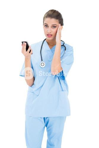 Confused brown haired nurse in blue scrubs using a mobile phone