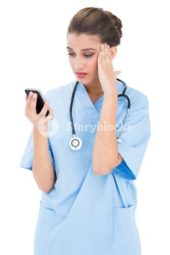 Puzzled brown haired nurse in blue scrubs using a mobile phone