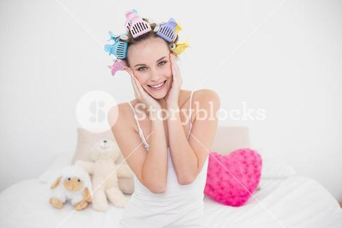 Relaxed natural brown haired woman in hair curlers touching her face