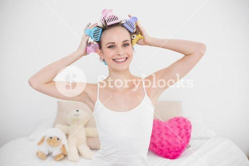 Pleased natural brown haired woman fixing her hair curlers