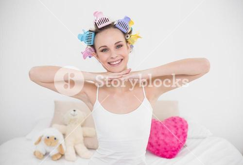 Joyful natural brown haired woman in hair curlers posing looking at camera