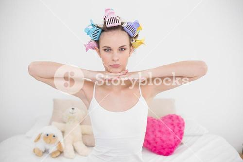 Serious natural brown haired woman in hair curlers posing looking at camera