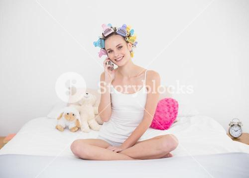 Delighted natural brown haired woman in hair curlers making a phone call