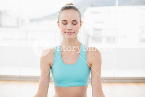 Sporty smiling woman sitting with closed eyes