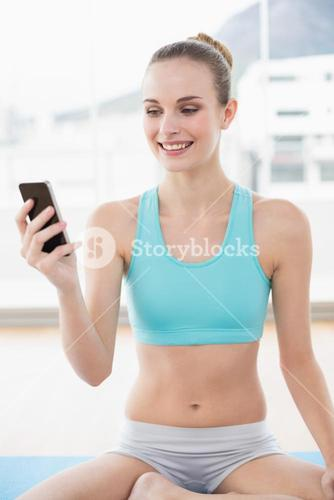 Sporty cheerful woman holding phone while sitting on exercising mat