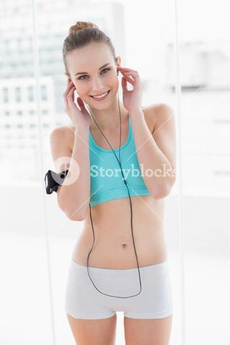Sporty smiling woman listening to music