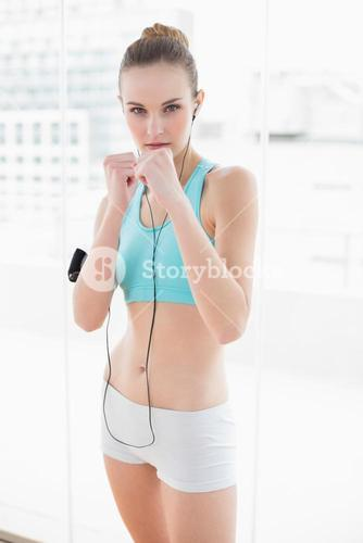 Sporty serious woman listening to music