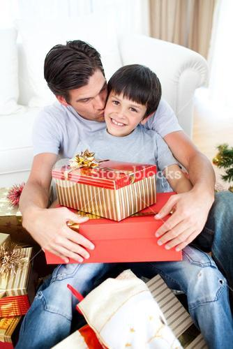 Father kissing his son after giving him a Christmas gift