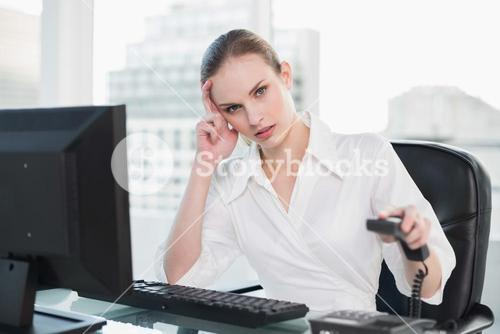Frowning businesswoman sitting at desk hanging up phone