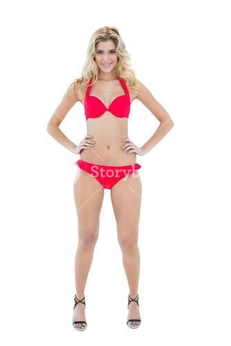 Cheerful smiling blonde model posing with hands on hips wearing red bikini