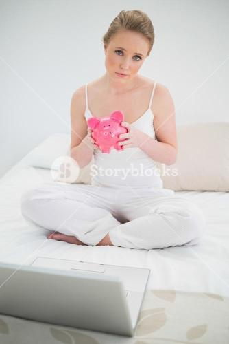 Natural serious blonde holding piggy bank while sitting on bed