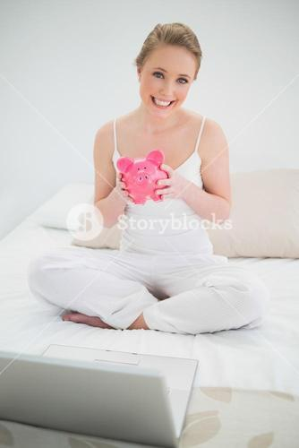 Natural smiling blonde holding piggy bank while sitting on bed