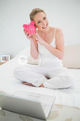 Natural cheerful blonde holding piggy bank while sitting on bed