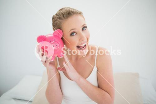 Natural excited blonde holding piggy bank while sitting on bed