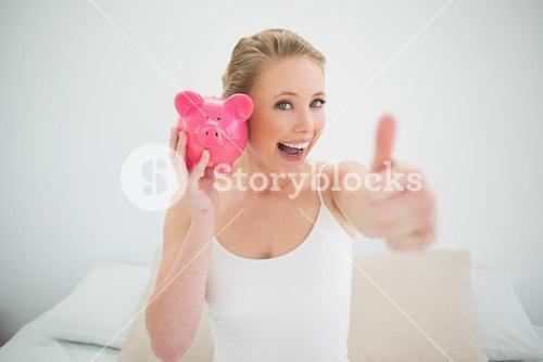 Natural happy blonde holding piggy bank while sitting on bed