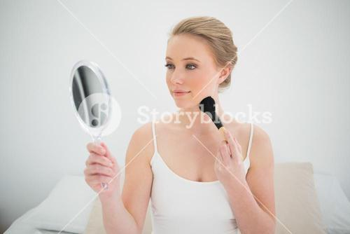 Natural content blonde holding mirror and using brush