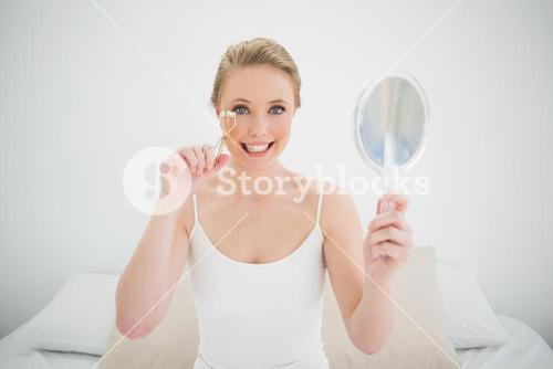Natural happy blonde holding mirror and using eyelash curler