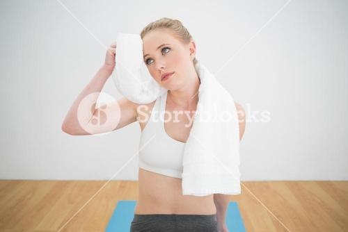 Thoughtful sporty blonde touching forehead with towel