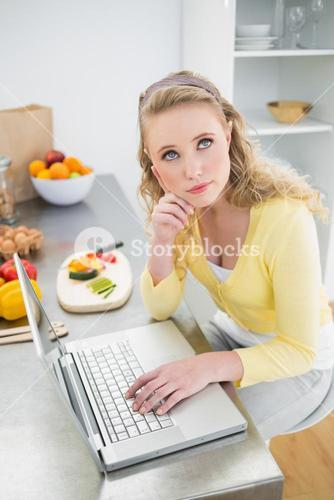 Day dreaming cute blonde using laptop