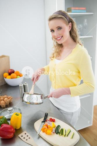 Smiling cute blonde stirring with wooden spoon