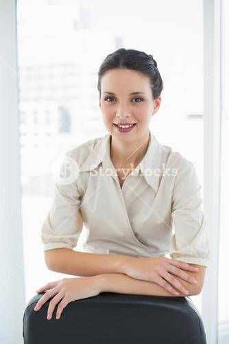 Pleased stylish brunette businesswoman posing looking at camera