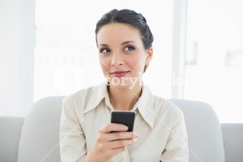 Dreamy stylish brunette businesswoman using her mobile phone