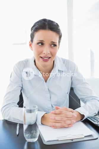 Skeptical stylish brunette businesswoman joining her hands and looking away