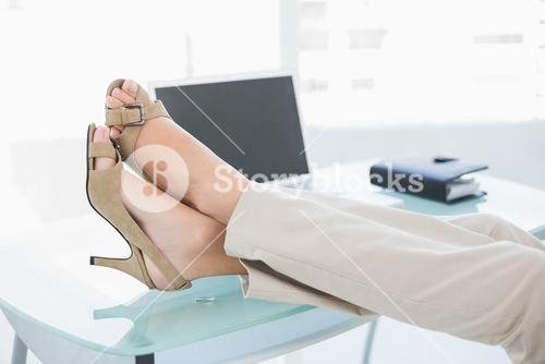Close up of a businesswoman in high heels relaxing with feet up