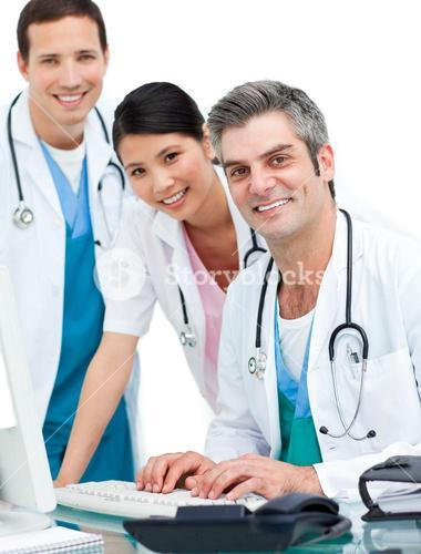 Smiling doctors and nurse working at computer