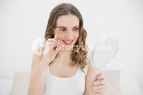 Woman using an eyelash curler while looking into a mirror