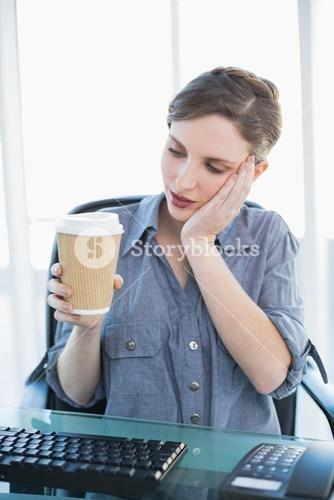 Tired businesswoman holding a disposable cup