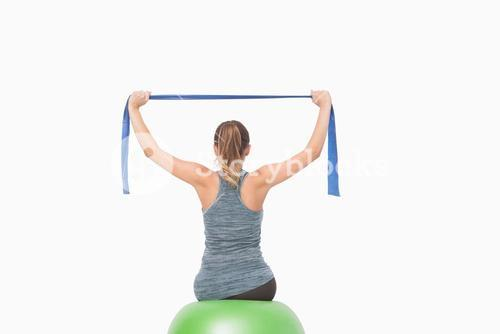 Ponytailed woman training using a resistance band sitting on a fitness ball