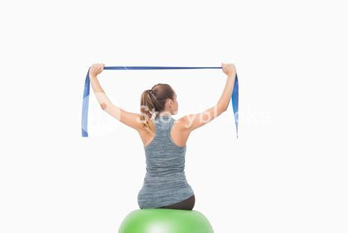Blonde woman sitting on a fitness ball training with a resistance band