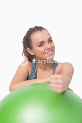Cheerful sporty woman showing thumbs up