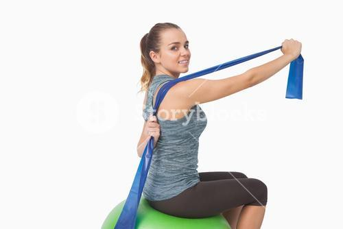 Pretty fit woman stretching her arms with a resistance band