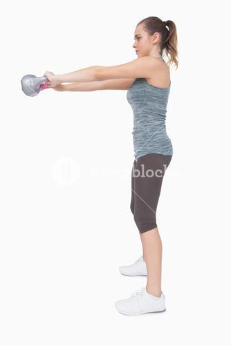 Young woman working with a kettle bell