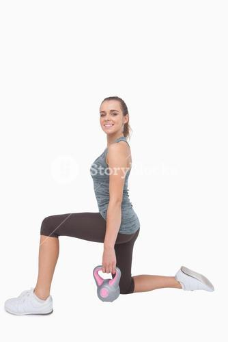 Cheerful woman lunging and using a kettle bell