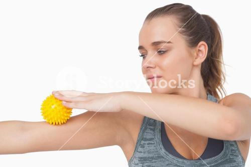 Woman using a massage ball for her arms