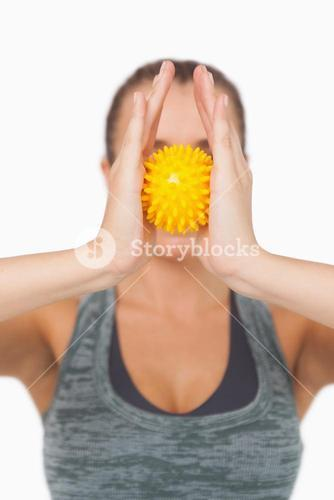Young woman holding yellow massage ball between hands