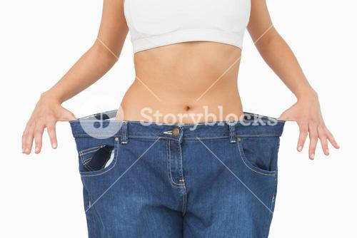 Mid section of young slim woman wearing too big jeans