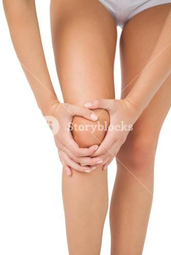 Slim young woman touching her injured knee