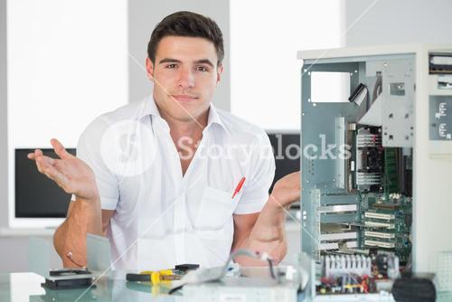 Confused computer engineer sitting behind open computer