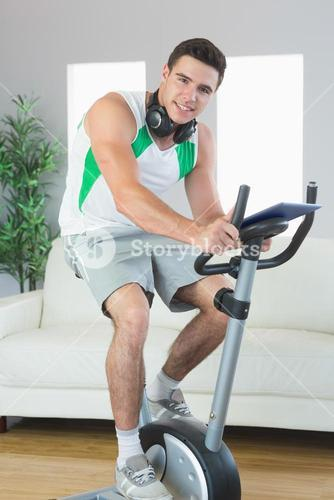 Content handsome man training on exercise bike using tablet