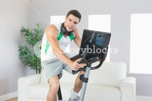 Content handsome man training on exercise bike using laptop