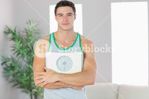 Content handsome man holding scales