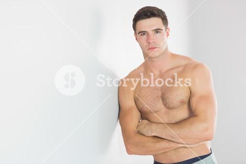 Sexy handsome man leaning topless against wall