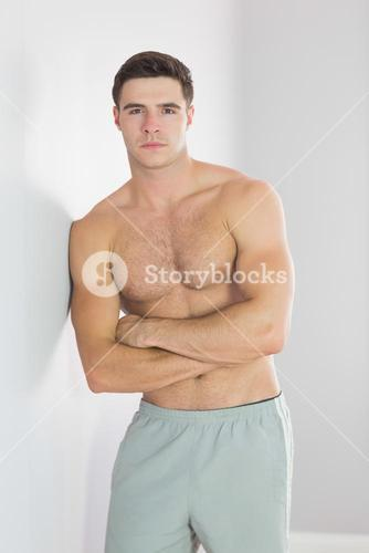 Serious handsome man leaning topless against wall