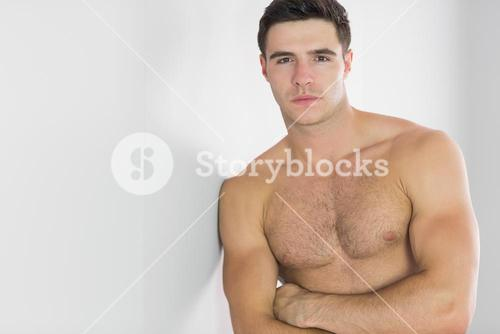 Stern handsome man leaning topless against wall