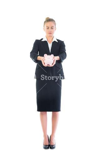 Chic businesswoman holding a piggy bank